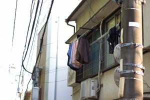 窓に洗濯物を干しているアパートの一室を通りから見たところ