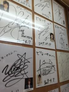 アメリカ村のたこ焼き屋「どないや」店内の有名人や芸能人のサインが貼られた壁